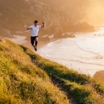 Man practicing trail running and leaping in a path in the coast