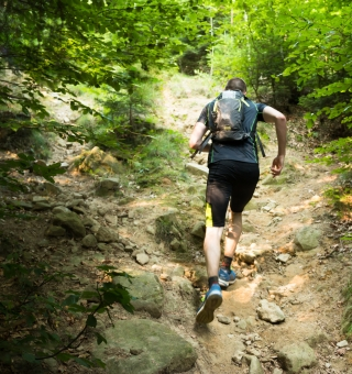 trail runner with backpack running up the steep hill