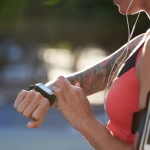Sporty tattoo woman with fitness tracker sports watch