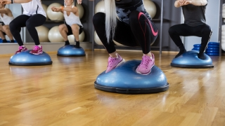 Friends Performing Squatting Exercise On Bosu Ball In Gym