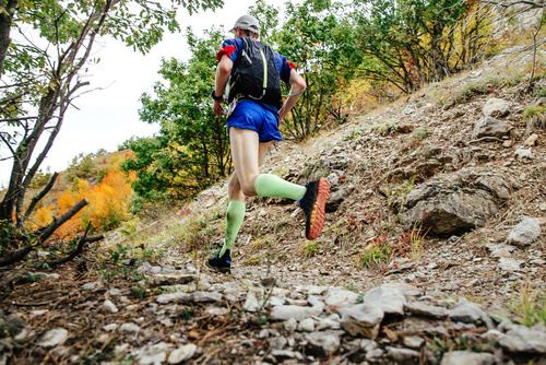 male runner in compression socks running on a mountain trail. ba