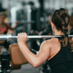 Woman in the gym . Woman exercising in gym with olympic barbell