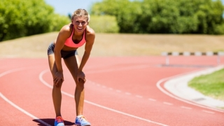 Tired female athlete standing on running track